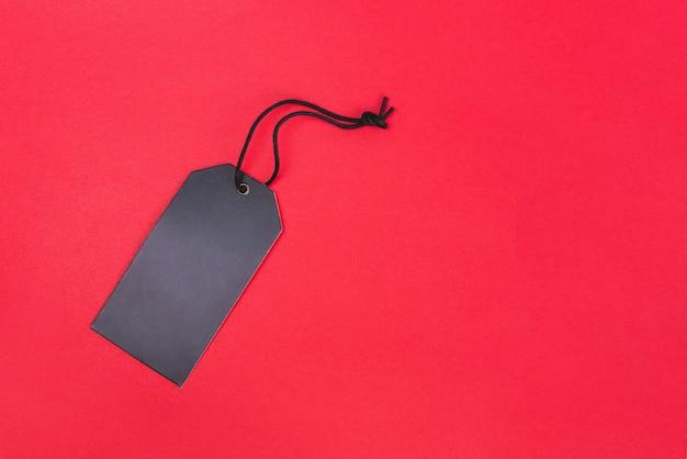 赤の背景にコピースペースで空白の黒タグ。値札、ギフトタグ、セールタグ、住所ラベル Premium写真