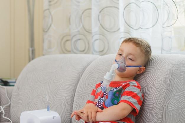 Кавказский мальчик вдыхает пары, содержащие лекарства, чтобы остановить кашель. Premium Фотографии