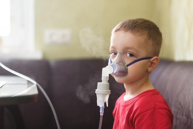 Маленький мальчик делает терапевтические ингаляции Premium Фотографии