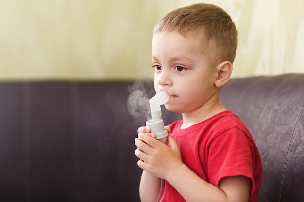 小さな男の子は治療用吸入をします Premium写真