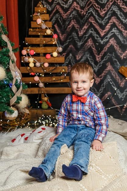 クリスマスフォトセッションでポーズをとる小さな男の子 Premium写真