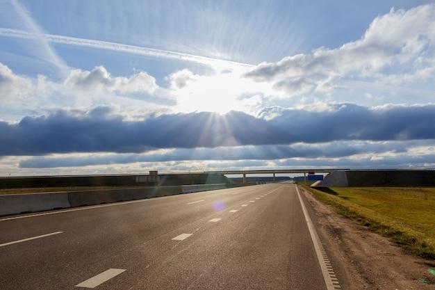 青い雲と輝く太陽の下の高速道路と高架橋。 Premium写真