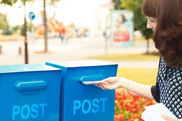 Женщина кладет письма в почтовый ящик Premium Фотографии