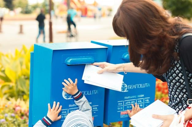 Малышка помогает маме класть письма в почтовый ящик Premium Фотографии