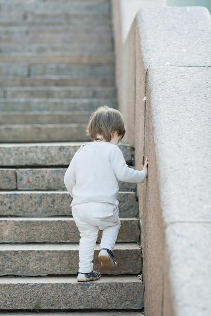 石造りの階段の前に立っている男の子。 Premium写真