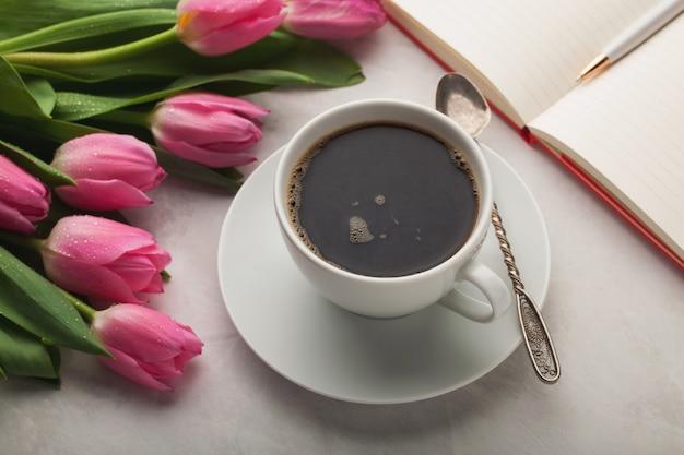 コーヒーのマグカップと女性作業机。 Premium写真