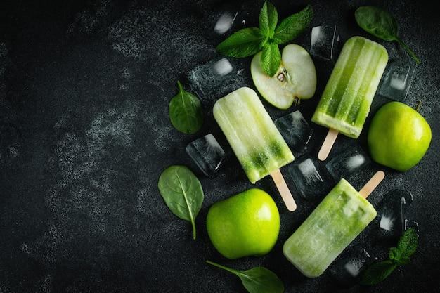 緑のりんごの明るい夏のアイスキャンディー。 Premium写真
