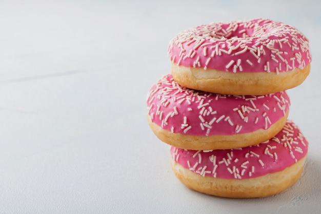 粉砂糖のピンクのドーナツ。 Premium写真