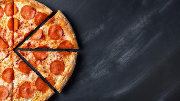 Вкусная пицца пепперони на черном бетонном фоне Premium Фотографии