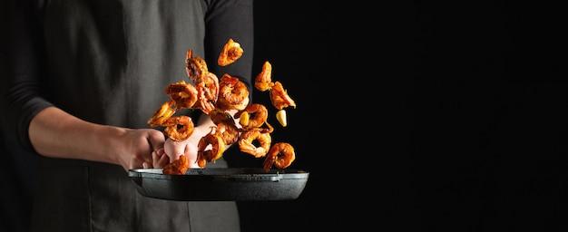 Профессиональный шеф-повар готовит креветки или лангустины Premium Фотографии