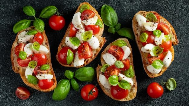 トマト、モッツァレラチーズ、バジルのブルスケッタ。 Premium写真