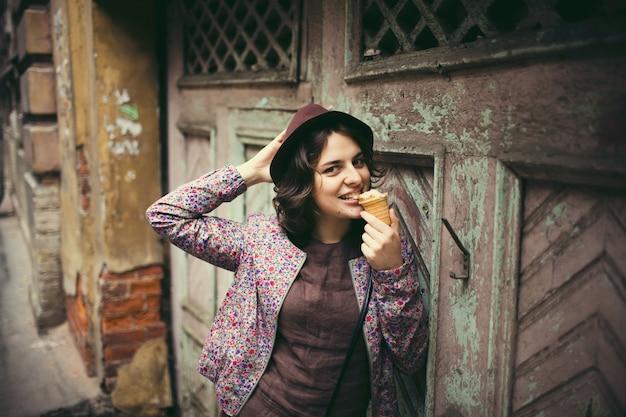 アイスクリームを食べる帽子の幸せな女の子。 Premium写真
