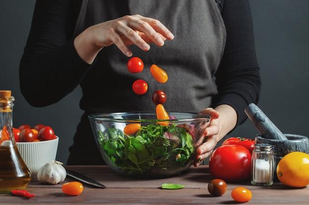 Шеф-повар наливает помидоры черри в миску Premium Фотографии