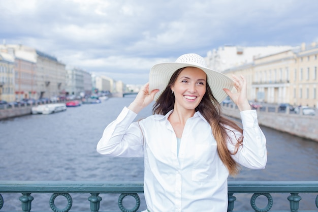 Красивая и улыбающаяся девушка в белой шляпе. Premium Фотографии