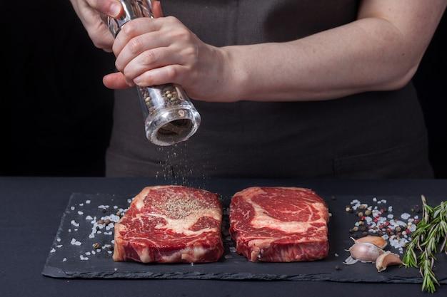 女性シェフがビーフステーキを用意しています。 Premium写真