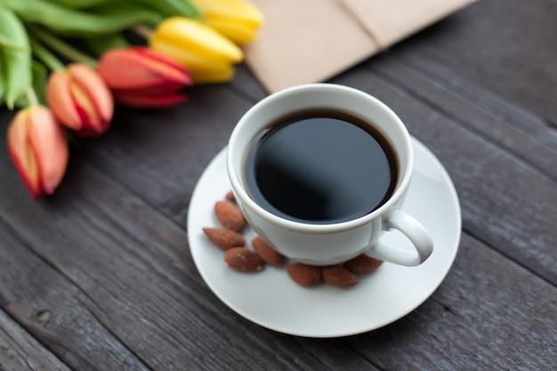 黄色とオレンジ色のチューリップとコーヒーの白いカップ。 Premium写真