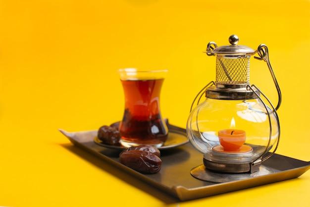 ラマダンカリームお祝い、オリエンタルキャンドルランプと紅茶のカップを皿に日付のクローズアップ Premium写真