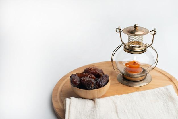 ラマダンカリームフェスティバル、キャンドルランプと木製のボウルに日付 Premium写真