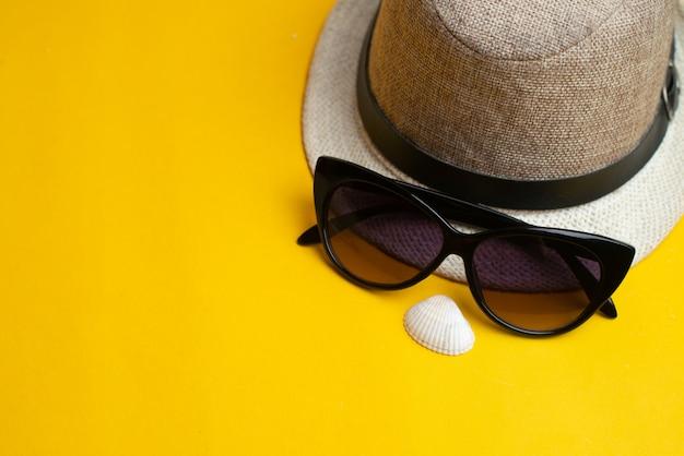 夏用アクセサリー、貝殻、帽子、サングラス。夏休みと海のコンセプト。 Premium写真