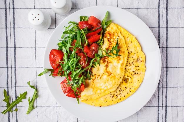 チーズとトマトのサラダと白プレート、上面の古典的なオムレツ。 Premium写真
