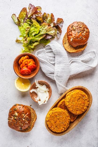 白い背景、平面図のビーガンバーガーのための原料。野菜のハンバーガー、アボカド、野菜とパン。 Premium写真
