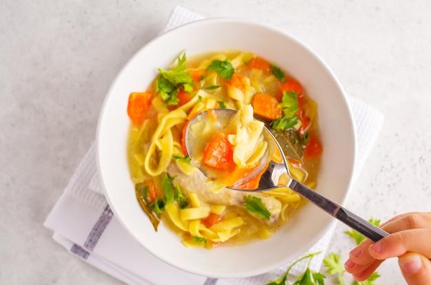チキンヌードルスープと白い背景の上の白いボウルに野菜。 Premium写真