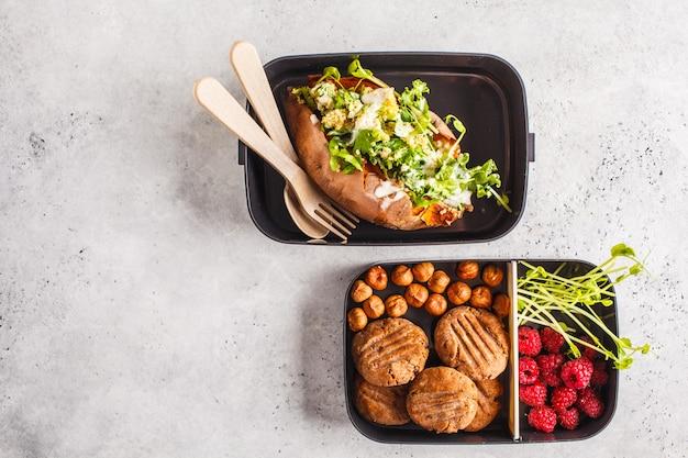 キノアの入った健康的な食事準備容器詰められたサツマイモ、クッキーとベリー、コピースペースでオーバーヘッドショット。 Premium写真
