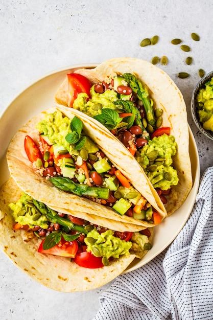 キノア、アスパラガス、豆、野菜、ワカモレのビーガントルティーヤ。 Premium写真