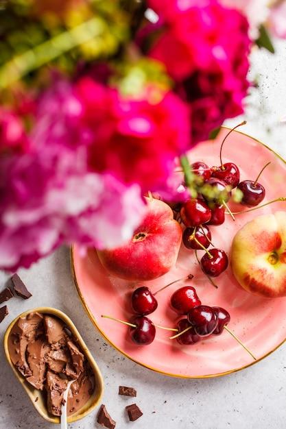 花、チョコレートデザート、ピンクのプレートの果実。 Premium写真