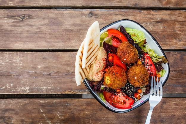 木製のテーブル、トップビューでボウルにフムス、ビーツと野菜のファラフェルサラダ。 Premium写真