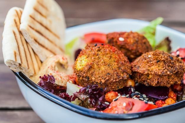 イスラエルの屋台。レストランのボウルにフムス、ビーツ、野菜を添えたファラフェルのサラダ。 Premium写真