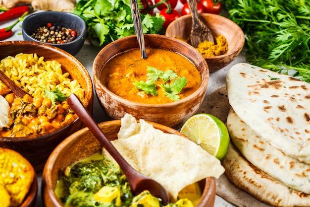 Даль, палак панир, карри, рис, чапати, чатни в деревянные чаши на белом столе. Premium Фотографии