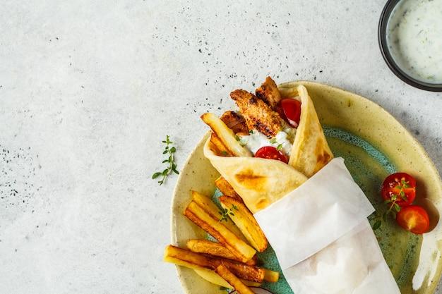 ジャイロスブラキは、鶏肉、ジャガイモ、ザジキソースを添えてピタパンに包みます。 Premium写真