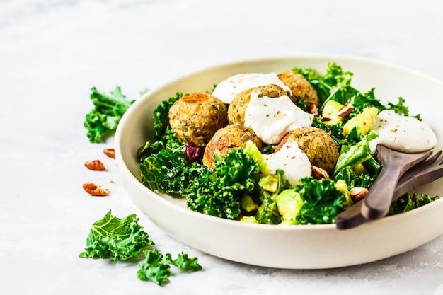 ビーガンレンズ豆のミートボールとグリーンケールサラダ、アボカド、タヒニドレッシングの白い皿。 Premium写真