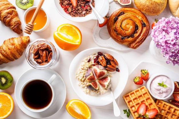 オートミール、ワッフル、クロワッサン、フルーツの朝食用テーブルのフラットレイアウト、 Premium写真