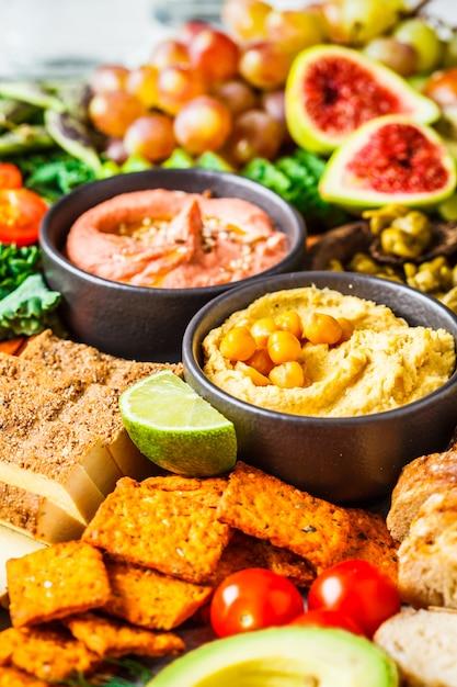 ビーガンの前菜盛り合わせ、フムス、豆腐、野菜、果物、パン Premium写真