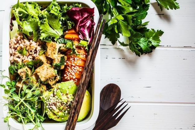 健康的なビーガンフード付きのランチボックス。米、さつまいも、豆腐、野菜が入った弁当箱。 Premium写真