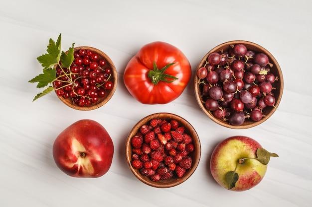 白地に赤の食品の品揃え、上面図。リコピンを含む果物と野菜。 Premium写真