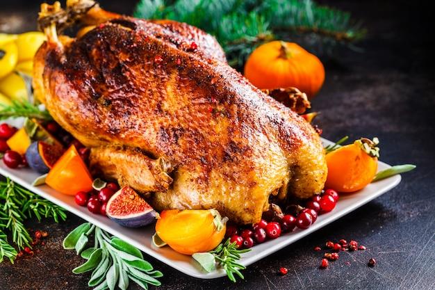 白い背景の灰色のプレートにフルーツとハーブ焼きクリスマス鴨 Premium写真