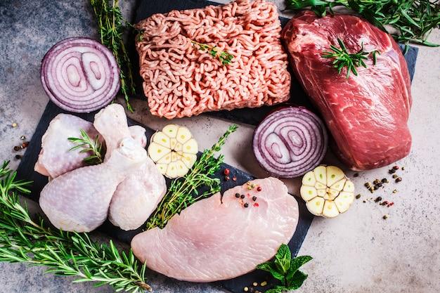 Концепция диета плотоядных животных. сырое мясо курицы, говядины, фарша и индейки на темном фоне, вид сверху, плоское положение. Premium Фотографии