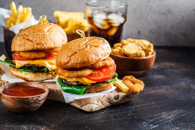 Чизбургеры, картофель фри, начос, пончики, сода и самородки Premium Фотографии