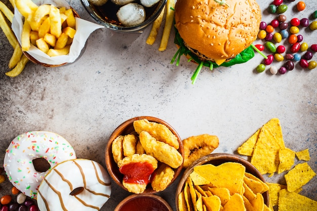 チーズバーガー、フライドポテト、ナチョス、ドーナツ、ソーダ、ナゲット Premium写真