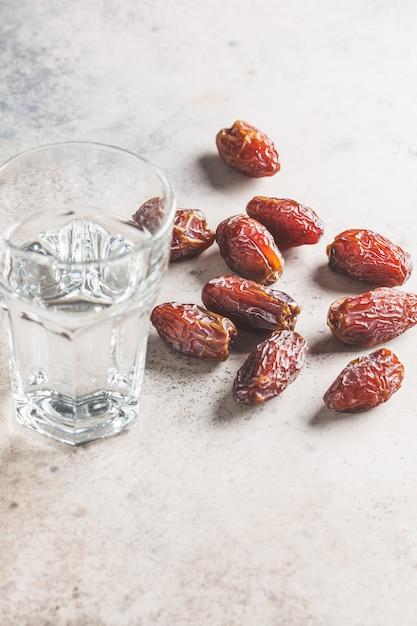 日付とコップ一杯の水、コピースペース。イフタール食品のコンセプト。 Premium写真