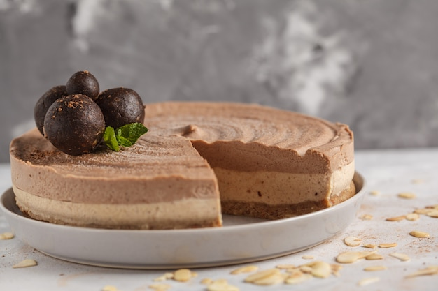 生ビーガンチョコレートキャラメルチーズケーキと生の甘いボール。健康的なビーガンフードコンセプト。明るい灰色の背景。 Premium写真