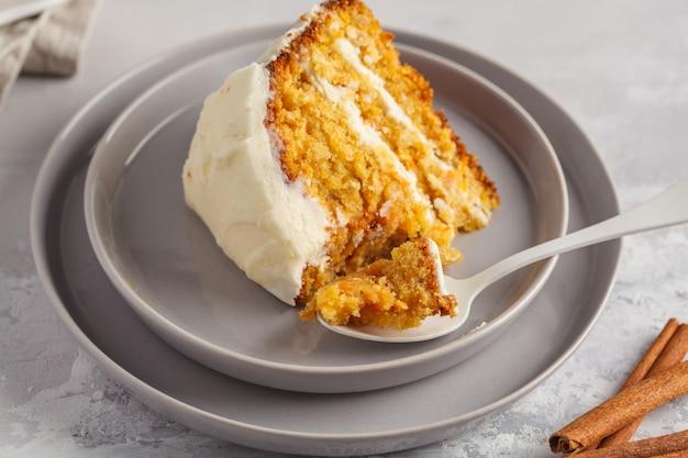 灰色の背景に白いクリーム(クリームチーズ)と自家製ニンジンの自家製ケーキ。お祝いデザートのコンセプト。 Premium写真
