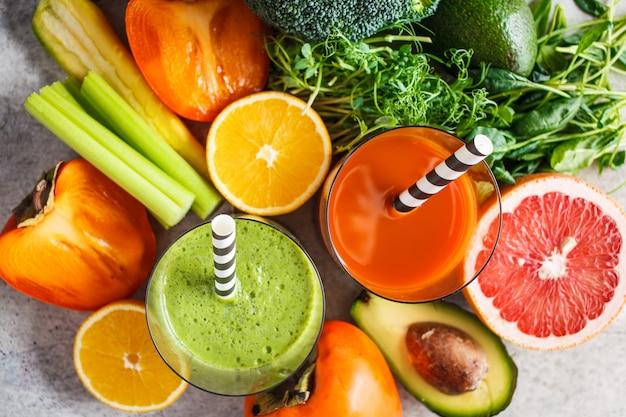 ガラスの緑とオレンジのデトックススムージー。デトックススムージー背景の成分。健康食品のコンセプト。 Premium写真