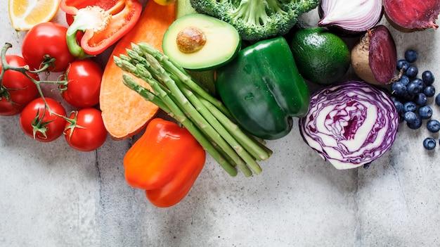 Радуга красит овощи и ягоды фон, вид сверху. детокс, веганская еда, ингредиенты для сока и салата. Premium Фотографии