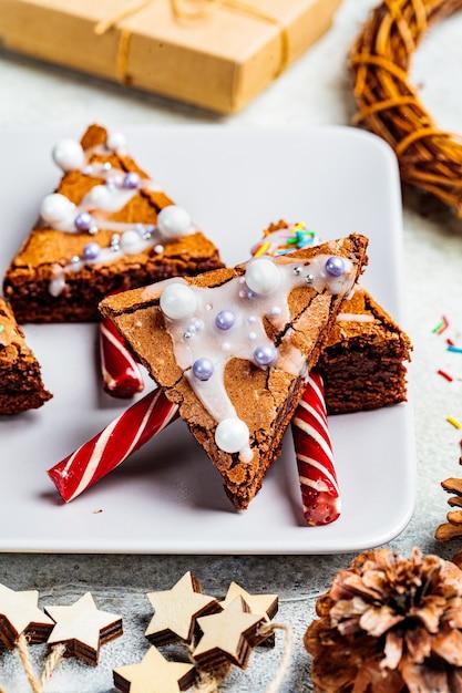キャンデー杖とアイシング、灰色の背景でクリスマスツリーブラウニー。クリスマス料理のコンセプトです。 Premium写真
