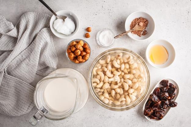 Ингридиенты для сырцового торта вегана, торта кешью на белой предпосылке. Premium Фотографии