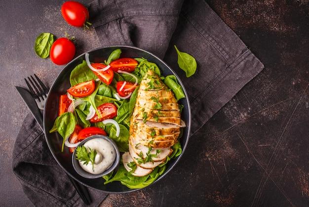 ほうれん草、トマト、シーザードレッシング、暗い背景と焼き鶏の胸肉サラダ。 Premium写真